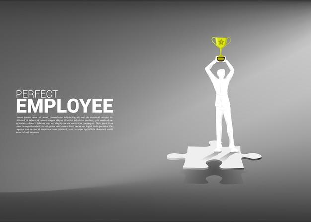 Silhouette d'homme d'affaires avec trophée debout sur le morceau de puzzle.