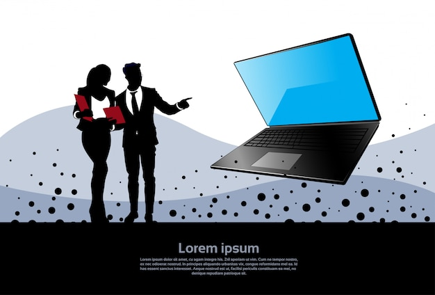 Silhouette homme et femme d'affaires pointent la main vers un ordinateur portable