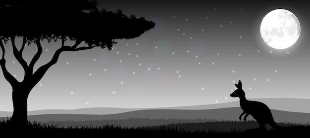 Silhouette un kangourou l'alimentation dans la nuit lumineuse