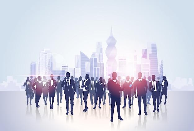Silhouettes de groupe de gens d'affaires sur la ville paysage des immeubles de bureaux