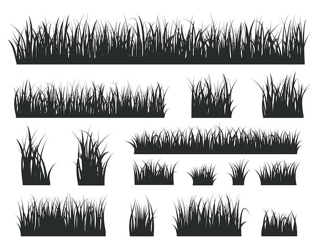 Silhouettes d'herbe. pelouses forestières à touffes noires. bordure de champ d'herbes naturelles isolées