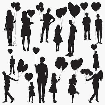 Silhouettes tenant des ballons en forme de coeur