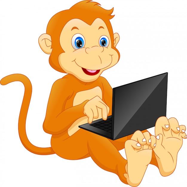 Singe mignon utilisant un dessin animé pour ordinateur portable