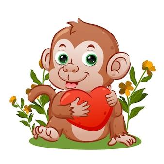 Le singe mignon avec le visage heureux est assis et tient le grand coeur de l'illustration