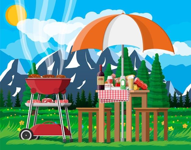 Soirée barbecue ou pique-nique. table avec bouteille de vin, légumes, fromage, canette de bière. gril électrique avec barbecue