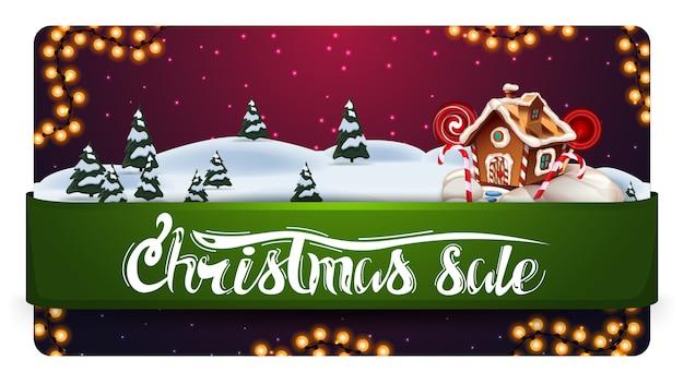 Soldes de noël, bannière d'escompte avec magnifique paysage d'hiver, ruban horizontal vert avec offre et maison en pain d'épice de noël