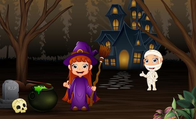 Sorcière d'halloween et maman avec maison effrayante dans la nuit