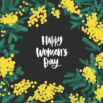 Souhait festif de la journée de la femme heureuse entouré de belles fleurs et feuilles de mimosa en fleurs ou d'acacia argenté.