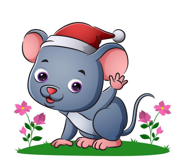 La souris porte le bonnet de noel et agite la main de l'illustration