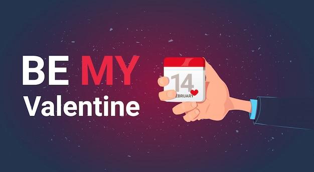 Soyez mon valentin carte de voeux avec la main tenant le calendrier 14 février concept de vacances d'amour de jour