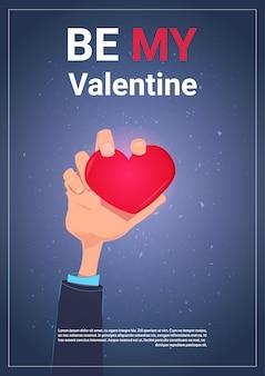 Soyez mon valentin carte de voeux avec la main tenant fond de modèle de coeur avec espace de copie