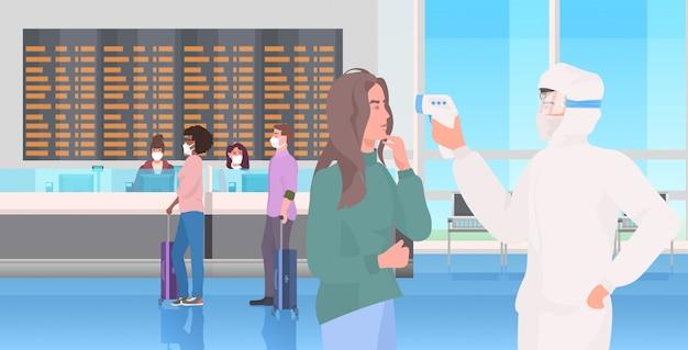 Spécialiste de la combinaison de matières dangereuses vérifier la température des passagers au terminal de l'aéroport pandémie de coronavirus