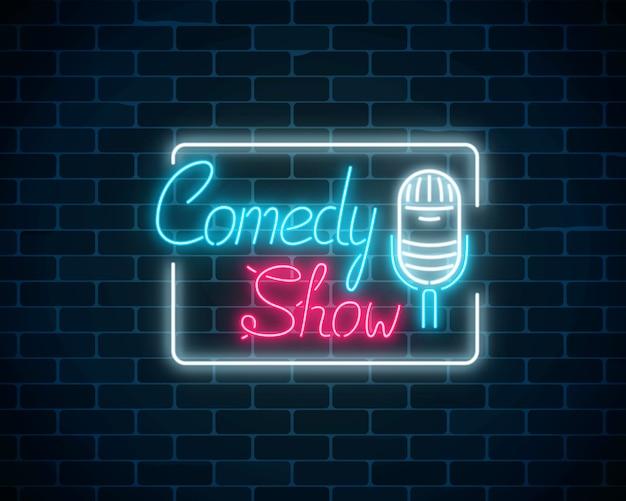 Spectacle de comédie au néon rougeoyant avec microphone rétro dans un cadre rectangulaire sur un fond de mur de brique.