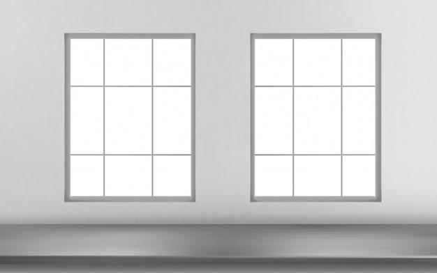Surface de table en acier devant des fenêtres sur mur blanc
