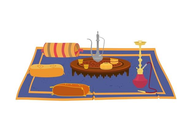 Table basse ronde asiatique avec théière et narguilé sur tapis avec coussins décoratifs colorés autour.