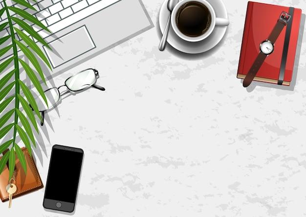 Table de travail de bureau vue de dessus avec des éléments de bureau avec des feuilles vertes