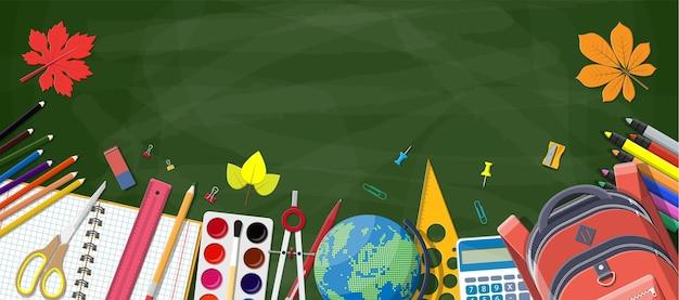 Tableau vert et fournitures scolaires.