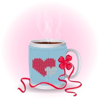 Tasse blanche dans une couverture tricotée avec motif coeurs.