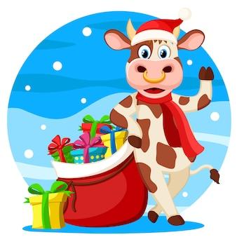 Un taureau avec un sac de cadeaux est dans un chapeau et une écharpe du nouvel an. année du taureau