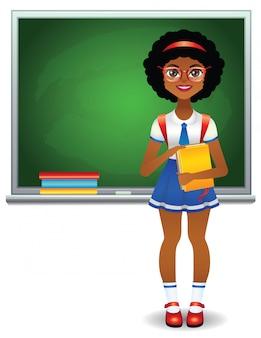 Teen girl standing in green school board avec des livres