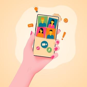 Téléphone faisant un appel vidéo dans une main féminine.
