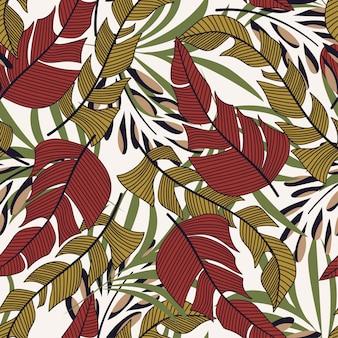 Tendance modèle sans couture avec les plantes et les feuilles tropicales colorées