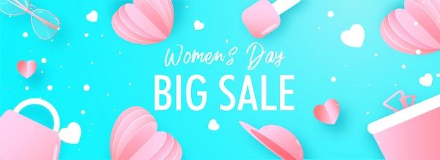 En-tête de grande vente ou conception de bannière avec des coeurs en papier rose, une boîte-cadeau, des lunettes, un sac à main et un vernis à ongles décoré sur fond bleu pour la journée de la femme.