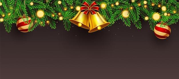 En-tête de site web ou bannière décorée avec une clochette dorée, des feuilles de pin, des babioles et une guirlande lumineuse sur une surface brune.