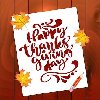 Texte de calligraphie happy thanksgiving day sur une feuille de papier avec des feuilles de l'automne