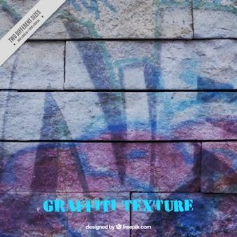 Texture d'un mur de briques peintes avec des graffitis