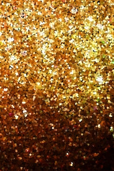 Texture de paillettes dorées sur fond noir. particules brillantes rondes et chatoyantes. effet d'explosion de paillettes dorées. confettis scintillants brillants. bannière, affiche, conception de carte de voeux brillant vecteur toile de fond