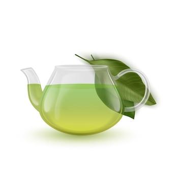 La théière en verre avec du thé vert et des feuilles