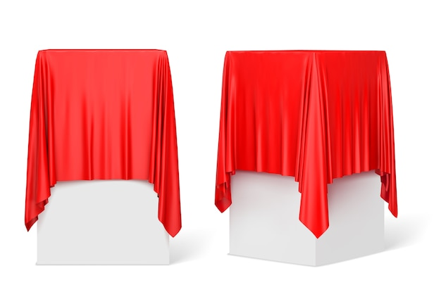 Tissu rouge sur un piédestal carré isolé sur blanc.
