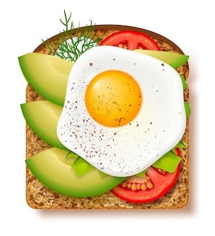 Toast à l'avocat avec tranches fraîches d'avocat mûr, assaisonnement et aneth, tomate et œuf au plat. délicieux sandwich à l'avocat.