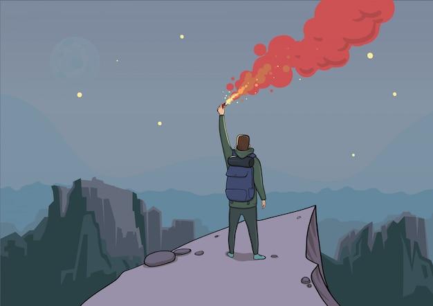 Le touriste avec la fusée éclairante sur une montagne regarde du haut.