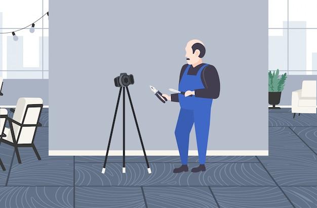 Travailleur bricoleur avec tournevis et pince coupante enregistrement blogueur vidéo en ligne avec appareil photo numérique sur trépied concept de blog de réseau social appartement moderne intérieur pleine longueur horizontale