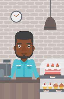 Travailleur debout derrière le comptoir à la boulangerie.
