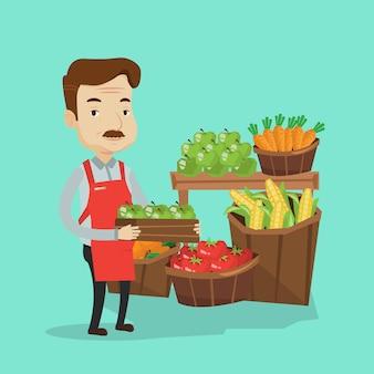 Travailleur de supermarché avec boîte pleine de pommes.