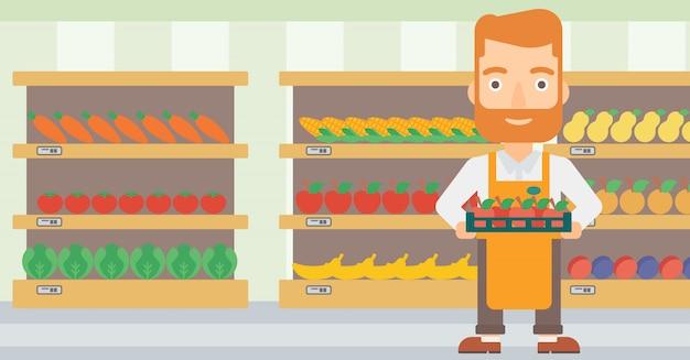 Travailleur de supermarché avec une boîte pleine de pommes.