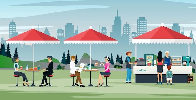 Travailleurs masculins et féminins mangeant dans un café en plein air