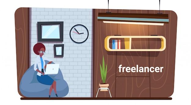 Travailleuse indépendante afro-américaine utilisant un ordinateur portable pour travailler dans un espace de travail créatif moderne