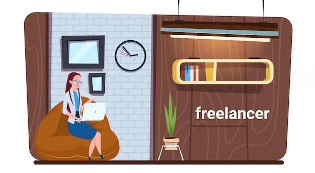 Travailleuse indépendante utilisant un ordinateur portable pour travailler dans un espace de travail créatif moderne