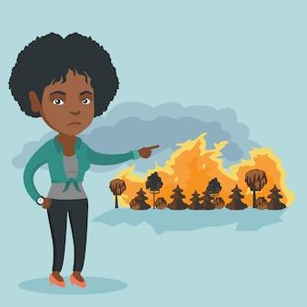 Triste femme pointant vers un feu de forêt.