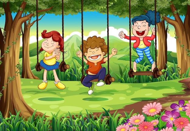 Trois enfants sur les balançoires dans les bois