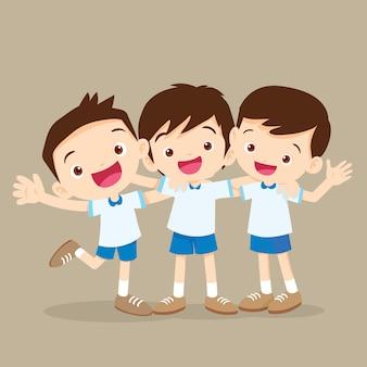 Trois garçons étreignant et souriant