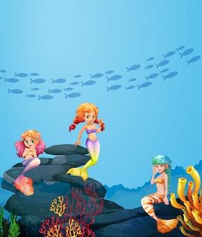 Trois sirènes nageant sous l'océan