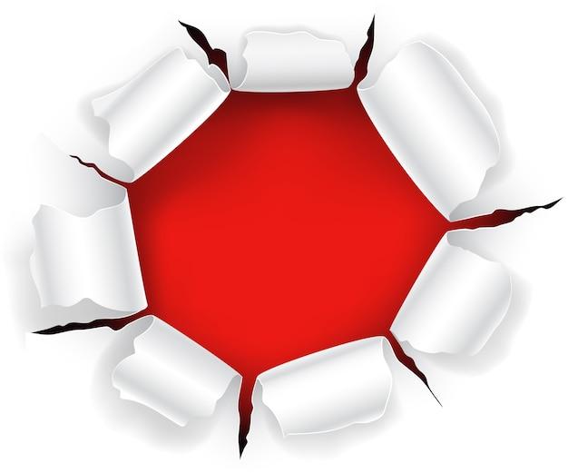 Trou rouge dans le papier avec les côtés déchirés.