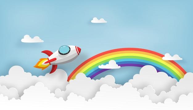 Un vaisseau spatial ou une fusée se lance dans le ciel au-dessus des nuages et de l'arc-en-ciel.