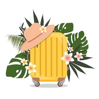 Valise jaune avec feuilles tropicales et chapeau de plage