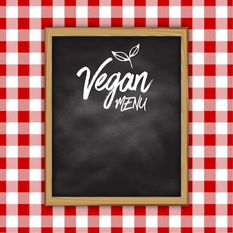 Vegan conception menu tableau noir sur un fond de tissu vichy